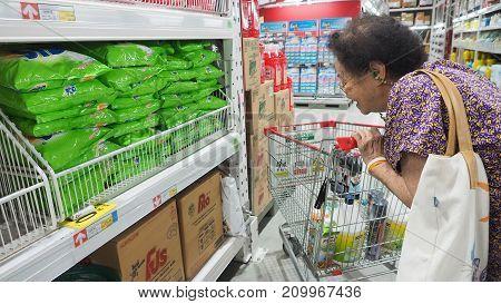 Grandma (my mother) see the washing powder price and pushing a shopping cart at Makro Sainoy branch Bangbuathong provice Thailand Asia 17 October 2017 01:00 PM.