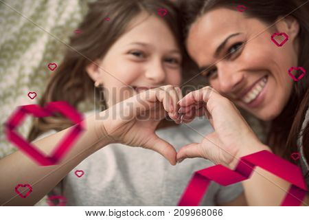 Hearts against mother and daughter making heart shape with hands while lying on bed