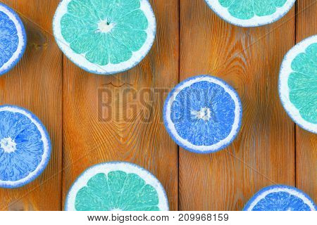Fresh half cut grapefruit and orange on a blue wooden background close up view
