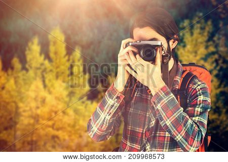 Hiker photographing through digital camera against autumn trees in forest