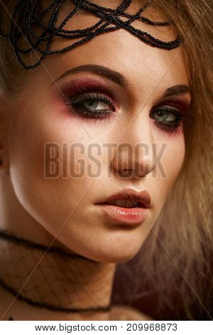 Closeup portrait of young woman in professional makeup in halloween style.