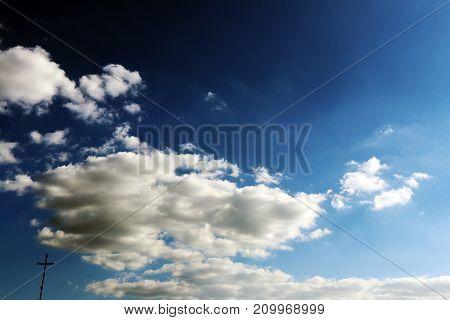 Contraste de luz e nuvens salientes coma presença de uma cruz