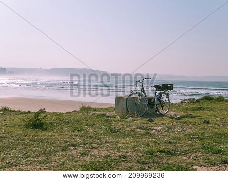 Bicycle is standing on the ocean beach. Toned photo.