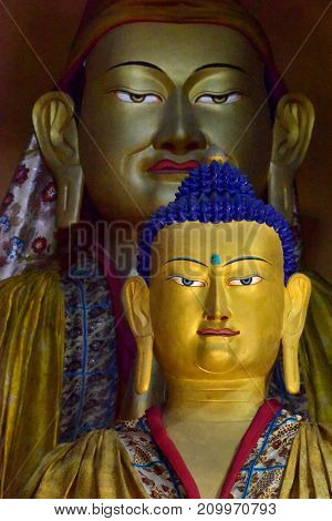 Two sculptures of Buddha in a Buddhist monastery in Zanskar: the yellow figure to the fore in the background is a huge ancient golden figure Buddha of Matreya Tibet.