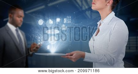 Businesswoman looking up while holding digital tablet against computer desks in the library