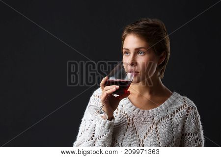 Beautiful girl with a glass of red wine on a black background. A girl with a short haircut drinks wine from a glass. Brunette. Close-up.