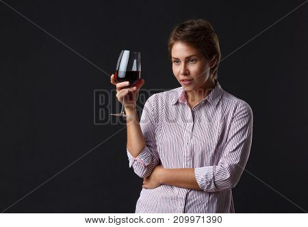 Beautiful girl with a glass of red wine on a black background. The girl with a short haircut. Brunette. Close-up.