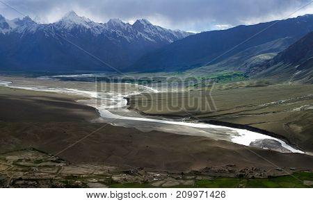 A wide mountain river to the high hills of the Pasduma Valley evening in Zanskar: the gloom fall on the valley in the background high chains of peaks with glaciers Northern India.