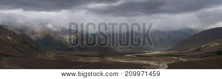 Thunderstorm in the highland river valley of Zanskar: heavy gray clouds fall on peaks the gloom envelops the hills panoramic photo the Himalayas Northern India.