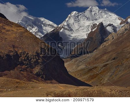 Autumn in the high mountains: huge cliffs are covered with glacial snows in the foreground are slopes with red grass Himalayas Tibet.