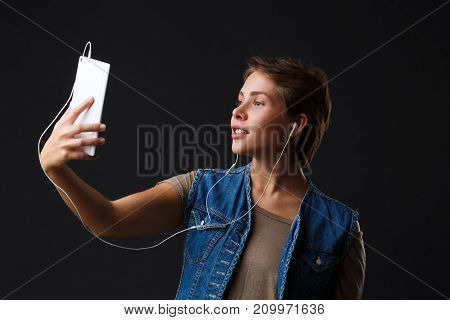 Beautiful girl with short hair in white headphones listens to music from her phone on a black background. He looks at his phone. Close-up.