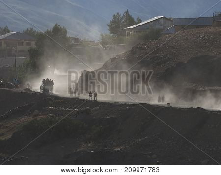 Evening in a mountain village: on a dusty road people return to their homes the sun's rays in a fog of dust and silhouette figures the Himalayas.