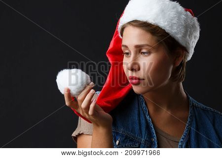 Young woman with short hair and red lips in santa hat on a black background. Close-up.