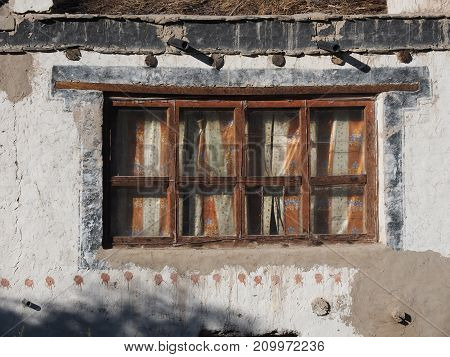 Vintage window of a rural house: old wooden brown frames through the glass cloth curtains are visible white clay wall.
