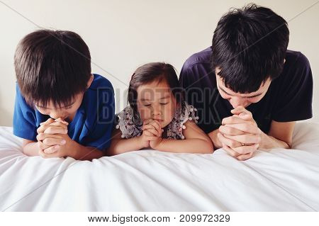 parent and childred praying on the bed