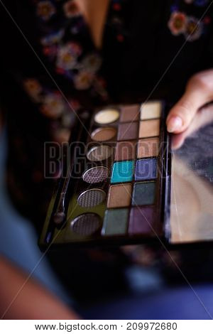 Cosmetic beauty procedures and makeover concept. Woman holds makeup professional palette. Make-up applying