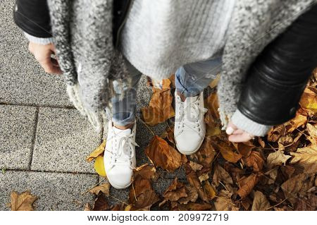 Young hipster woman is standing among autumn leaver wearing white sneakers. Top view. Autumn street fashion concept.