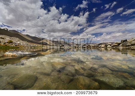 Summer on Lake Pangong: clear water sacred lake at the bottom of huge boulders in the background gently sloping brown mountains clear sky Himalayas Northern India.