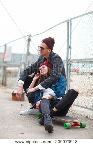 The guy with the girl is well fashionably dressed sitting, the guy hugs the girl