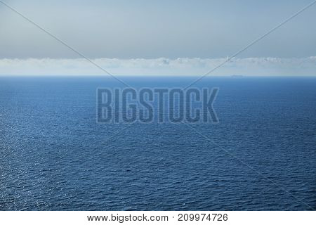 Blue sea, sky with clouds and ship silhouette.