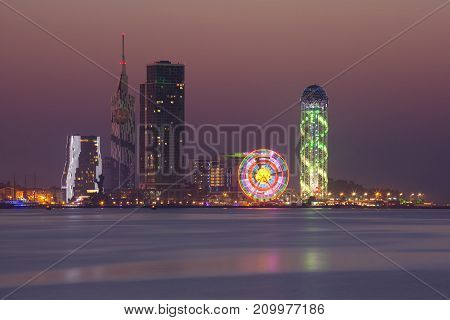 View from Sea Beach to Illuminated cityscape with Skyscrapers, ferris wheel and Alphabet Tower at night, Batumi, Adjara, Georgia