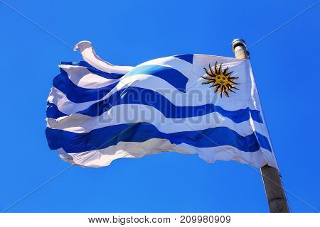 National flag of Uruguay flying in blue sky Montevideo