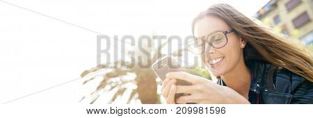 Portrait of trendy girl in town using smartphone- template