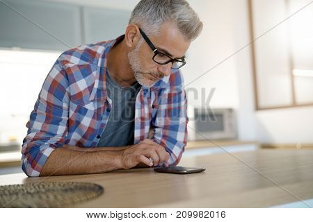 Middle-aged man at home using smartphone