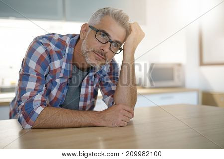 Middle-aged man with grey hair in home kitchen