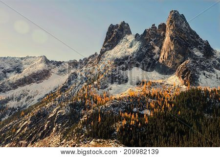 Autumn sunrise at North Cascades. Golden Larches on Early Winter Spires. Winthrop. Washington. United States.