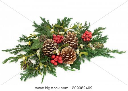 Christmas floral table decoration with holly, gold pine cones, ivy, mistletoe, cedar and juniper leaf sprigs on white background.