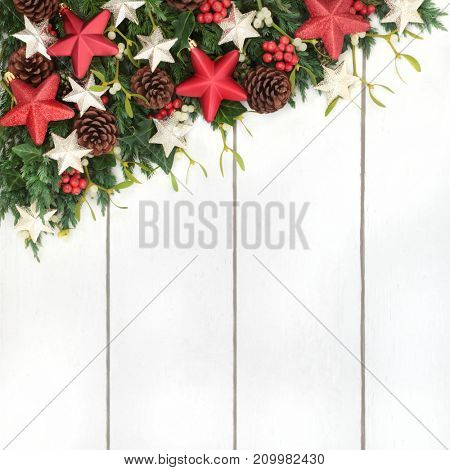 Christmas background border with bauble star decorations, holly, mistletoe, ivy, fir and pine cones on rustic white wood background.