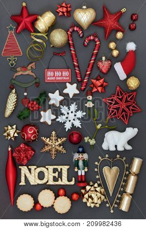Noel sign with symbols of christmas including bauble decorations, holly, mistletoe, mince pies, foil wrapped chocolates and gingerbread biscuits on grey background.