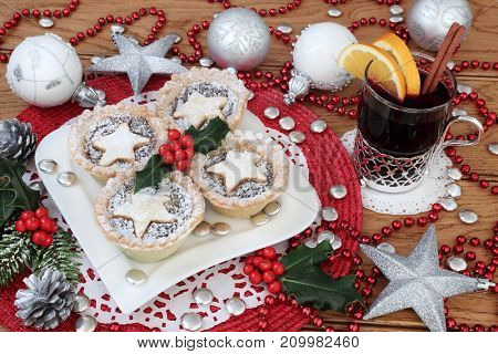 Christmas mince pies and holly on a heart shaped plate with mulled wine and bauble decorations on  oak table background.