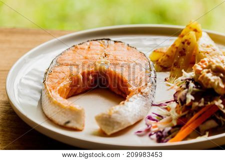 Salmon steak in a white plate on a wooden table.