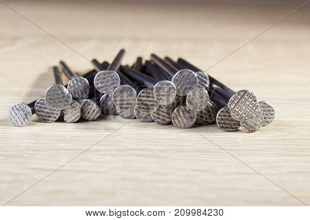 Heap of metal nails on a wooden table