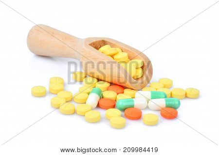 pill and capsules in wooden scoop isolated on white background