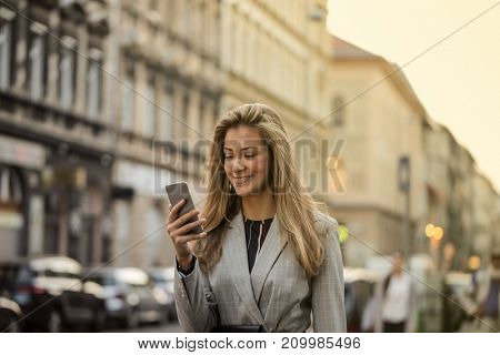 Beautiful blonde woman reading a text message