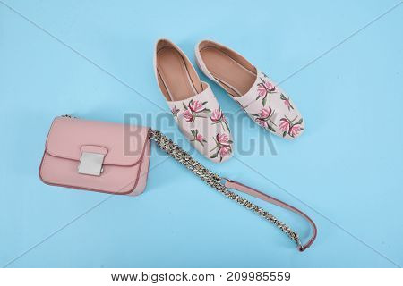 female floral shoes with handbag on blue background