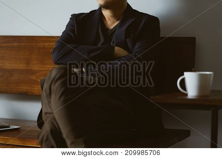 Businessman sit on wooden chair relax with coffee selective focusing .