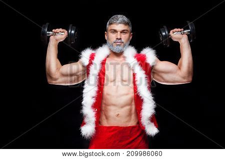 Holidays and celebrations, New year, Christmas, sports, bodybuilding, healthy lifestyle - Muscular handsome sexy Santa Claus. on a black background with dumbbells