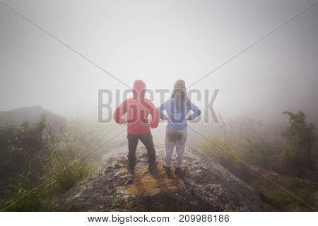 Hiking couple happy to reach the top of a mountain