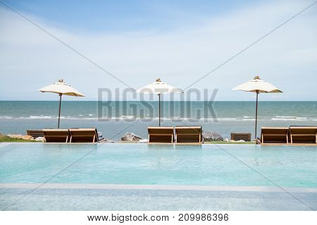 Outdoor swimming pool with umbrella and daybeds and beautiful sea view