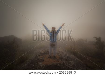 Happy woman standing on a cliff side