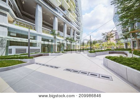 Low angle perspective view of empty pavement and modern office building with green eco concept .