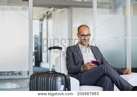 Mature businessman using mobile phone at the airport in the waiting room. Business man typing on smartphone in lounge area. Portrait of latin man sitting and holding passport with luggage.