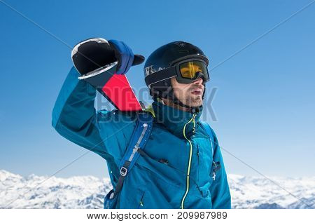 Pensive skier carrying ski on shoulders on the peak of the snowy mountain. Portrait of young thoughtful man looking snowy panorama before ski. Holiday and winter sport concept.