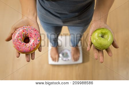 close up woman on weight scale holding in her hand apple fruit and donut as choice of healthy versus unhealthy food dessert in health care and nutrition concept and struggling to diet