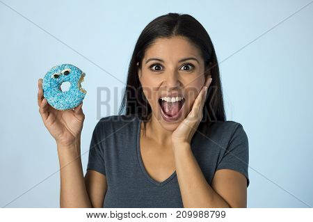 young happy attractive Latin woman smiling excited holding sugar donut isolated on blue background in sugar abuse nutrition and diet health care concept surrendering to temptation