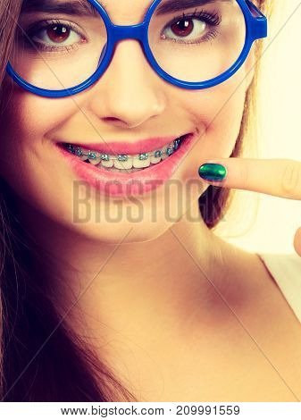 Dentist and orthodontist concept. Nerdy geek woman wearing big eyeglasses smiling showing her white teeth with blue braces